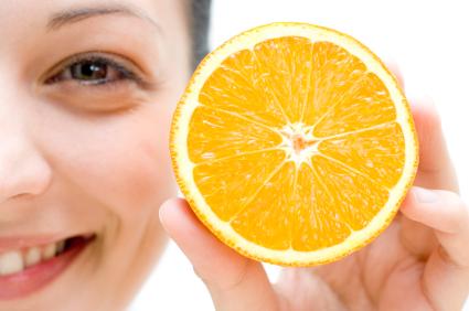 Chica sonriendo con media naranja en la mano